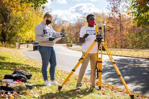 Students in Dr. Deborah Besser's Civil Engineering class wear masks and gloves while working together in groups and using surveying equipment alongside Mississippi River Boulevard. Liam James Doyle/University of St. Thomas