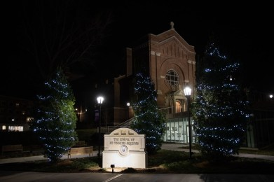 Holiday lights glow on trees in front of the Iversen Center for Faith and Aquinas Chapel.