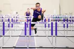 Evan Tenor leaps over hurdles during an indoor track meet in the Field House. Liam James Doyle/University of St. Thomas