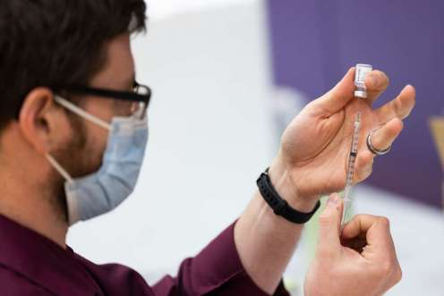 """A pharmacist fills vaccine doses during a vaccination clinic on the St. Paul campus in McCarthy Gym. """"We are grateful to the St. Thomas students, faculty and staff for the overwhelming response to the COVID vaccination clinics,"""" said McDermott. (Mark Brown/University of St. Thomas)"""