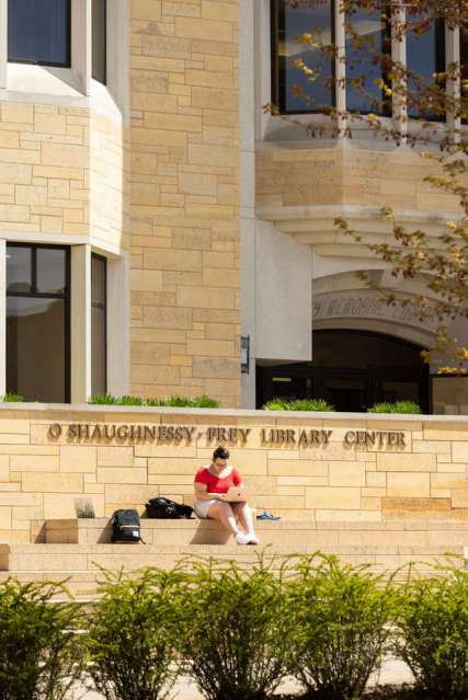 Junior Lizzy Sabel studies on the steps of the O'Shaughnessy Frey Library Center on a sunny spring day. Mark Brown/University of St. Thomas