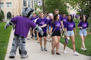 Students greet Tommie the mascot as they walk through the lower quad toward the annual March Out of the Arches event. Mark Brown/University of St. Thomas