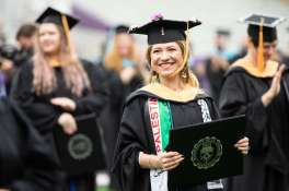 A student smiles at the commencement ceremony for graduate programs. Mark Brown/University of St. Thomas