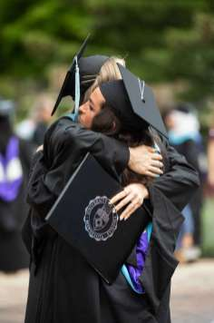 Students embrace after the commencement ceremony for graduate programs. Mark Brown/University of St. Thomas