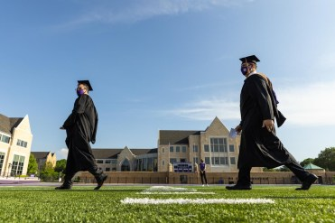 Students walk toward the stage during the commencement ceremony for graduate programs in the Opus College of Business and School of Engineering. Mark Brown/University of St. Thomas