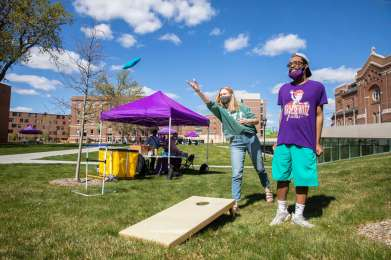 Students play bean-bag toss on the upper quad during a sunny spring afternoon. Liam James Doyle/University of St. Thomas