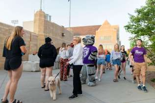 Tommie the mascot, University president Julie Sullivan and her dog Bella socialize with students. Liam James Doyle/University of St. Thomas