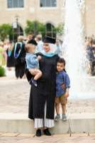 A student poses for a photo with children on Monahan Plaza after the commencement ceremony for graduate programs in the College of Arts and Sciences and the Morrison Family College of Health. Mark Brown/University of St. Thomas