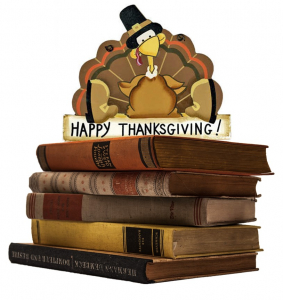 Happy Thanksgiving; a Turkey sitting on a stack of books.