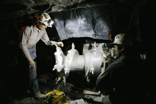 Miners servicing a continuous miner.