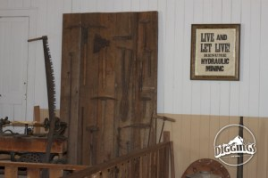 """Display of tools from the camp and a sign during the mining, urging """"Live and let live! Resume Hydraulic Mining."""""""
