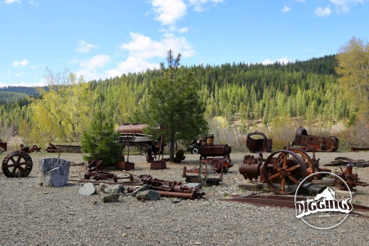 On the far side of the dredge is a yard full of rusting mining equipment at the Sumpter Valley Dredge State Heritage Area