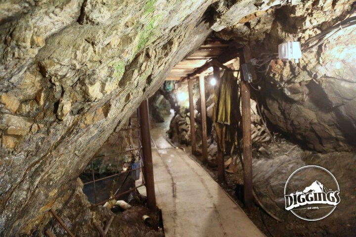 Walking through the  Crystal Gold Mine.  The original track for ore carts is still visible, embedded in the paved walkway.  To the right is an assortment of tools. the left is a flooded shaft that followed a vein deeper into the mountain.  To the right