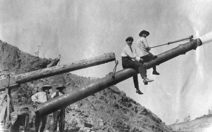 Men astride a giant (monitor) at La Grange hydraulic mine near Weaverville.
