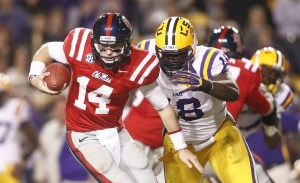 LSU Tigers defensive tackle Bennie Logan (18) reaches for Ole Miss Rebels quarterback Bo Wallace (14) during the second half at Tiger Stadium. LSU defeated Ole Miss 41-35. Photo Credit: Crystal LoGiudice-USA TODAY Sports