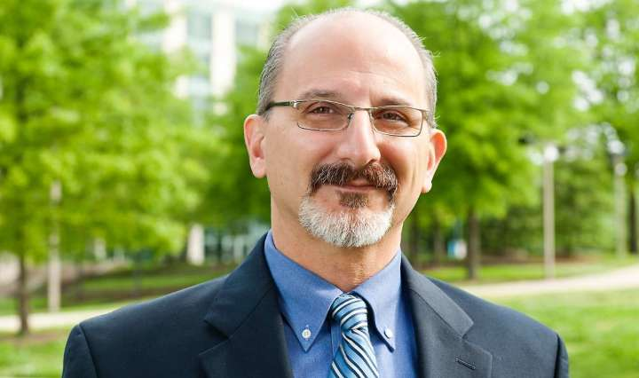 A man with a beard and mustache wearing dark rimmed glasses and a blue suit and striped tie smiles at the camera, there are green trees in the backgound