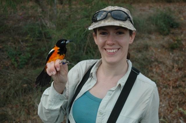 woman in outdoor gear holding a bird