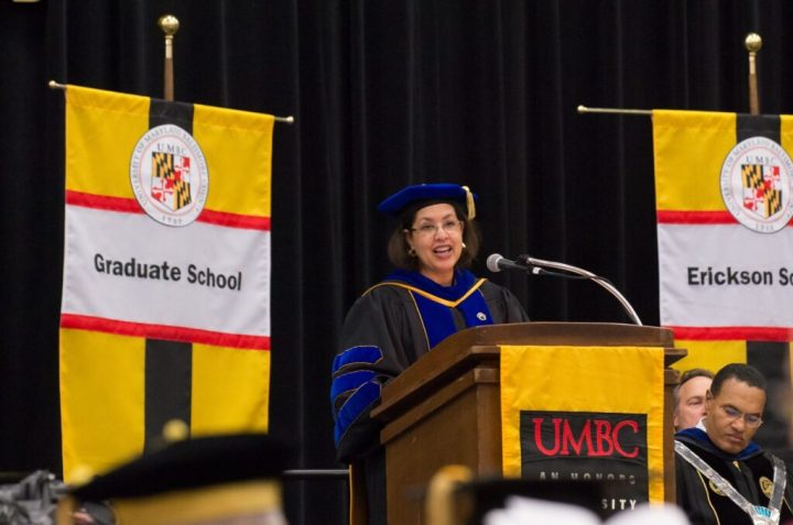 """Middle-aged black woman in Ph.D. regalia delivers remarks at a podium. Podium reads """"UMBC"""" Signs next to her read """"Graduate School"""" on left and """"Erickson"""" on right."""