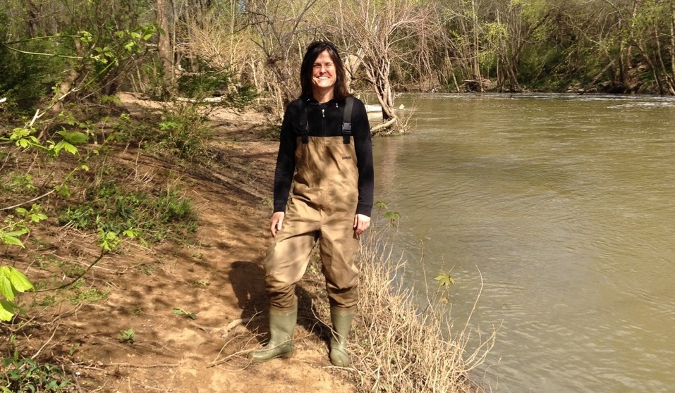 Middle-aged white woman with dark hair stands near water, wearing boots and waterproof overalls.