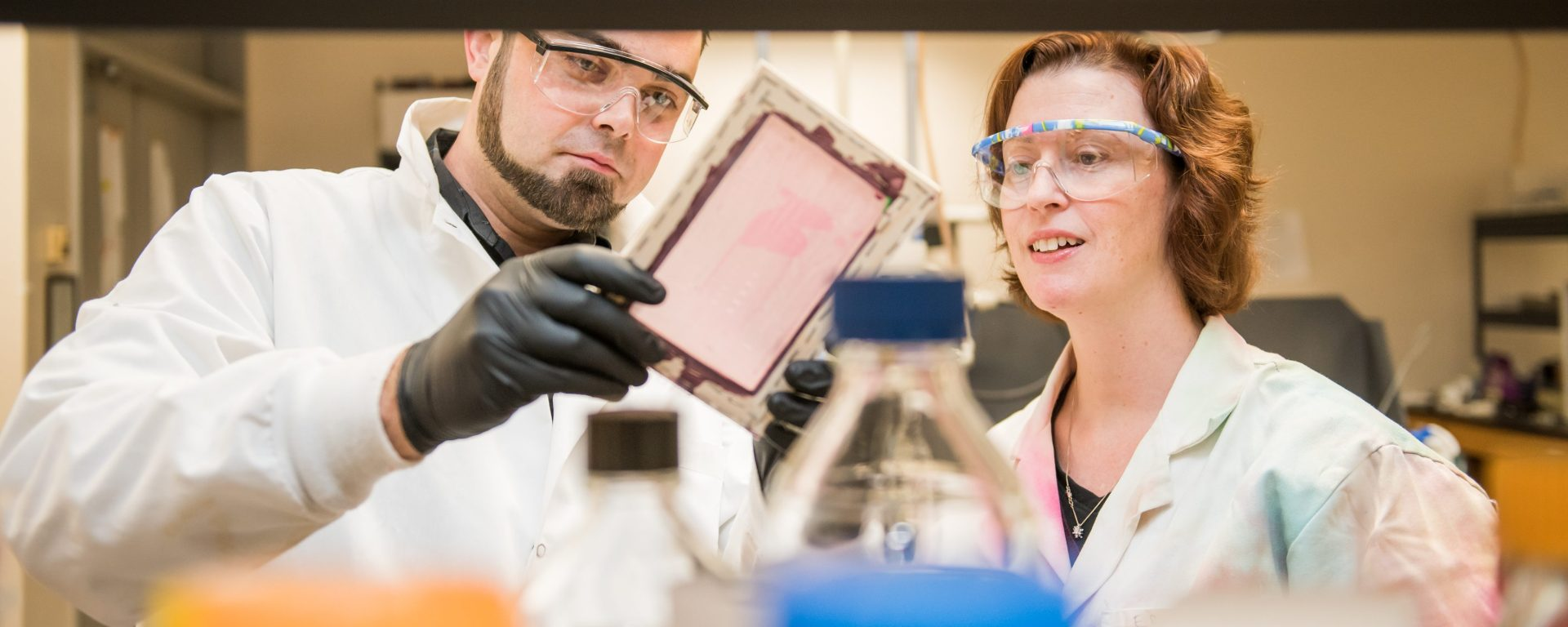 Man and woman look at equipment in a lab. Both wear lab coats and protective glasses.
