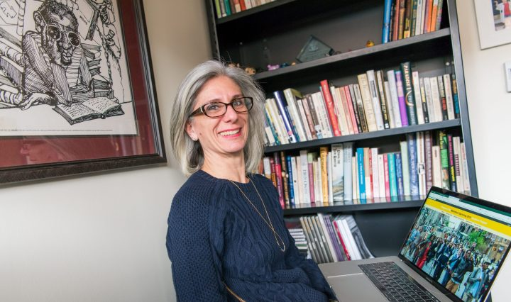 Researcher Denise Meringolo holding laptop displaying Baltimore Uprising digital collection