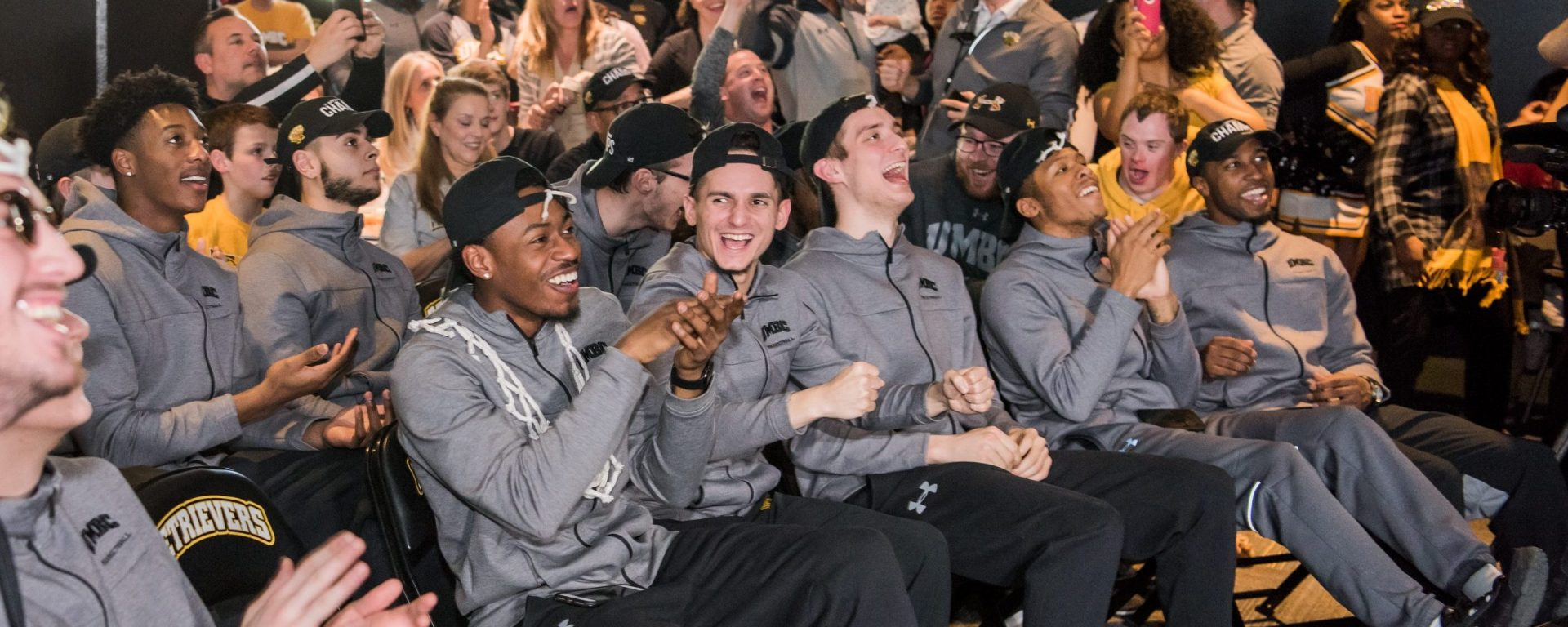 Basketball players seated, wearing gray jackets, smile while watching TV livestream.