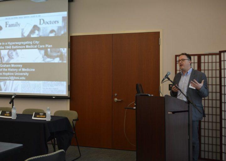 Presenter Graham Mooney stands behind a podium. Presentation slide visible on left side of image.