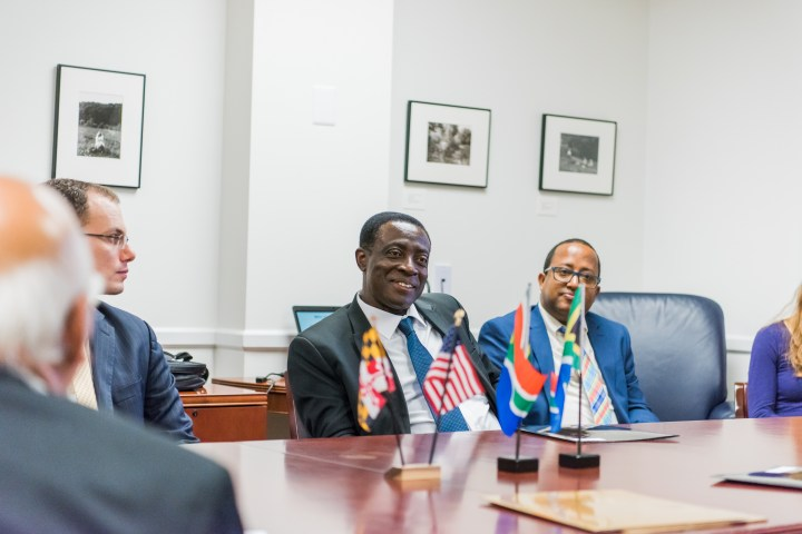 Three men in suits sit at a conference table. Flags of Maryland, U.S., and South Africa appear on the table.