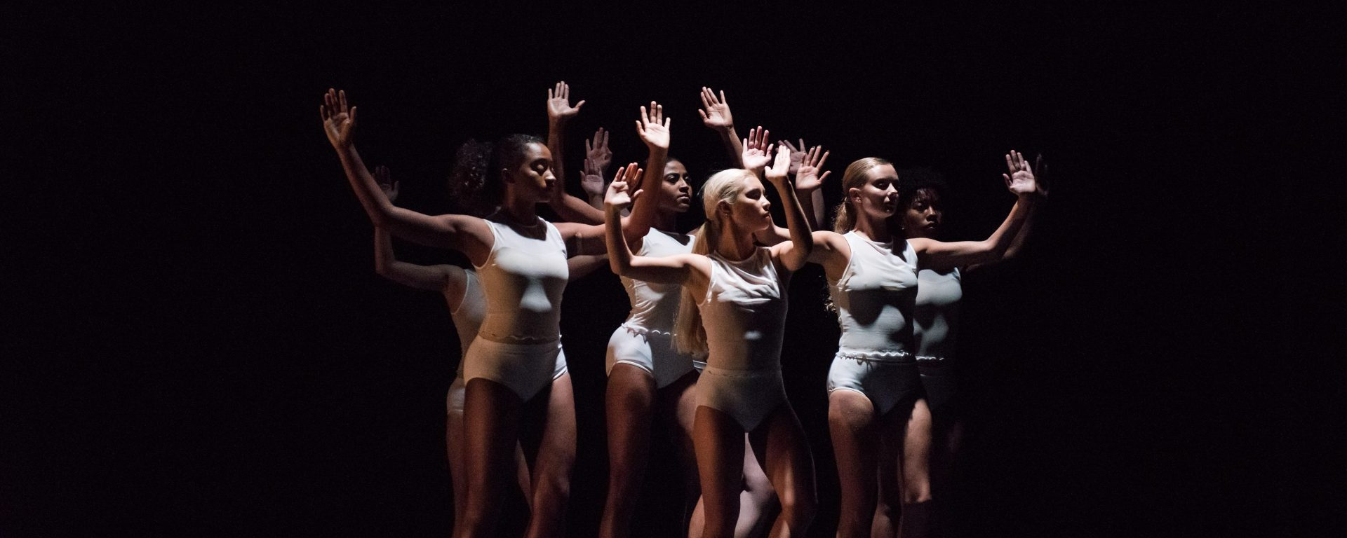 A group of women dancers performs, clustered together with arms in the air, with simple, white costumes and black background.
