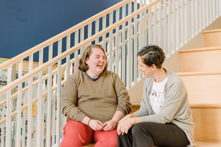 Two people sit, talking and smiling, on steps in the UMBC Commons.
