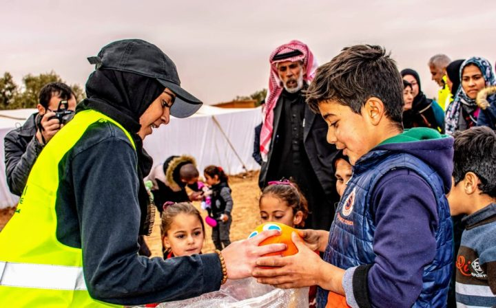 Maheen Haq giving out toys to children in a Syrian refugee camp. Photo courtesy of Haq with permission from Helping Hand for Relief and Development.