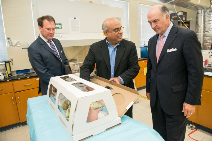 Three men in suits are in a lab gathering around a table looking at a cardboard box with a baby doll inside simulating an incubator.