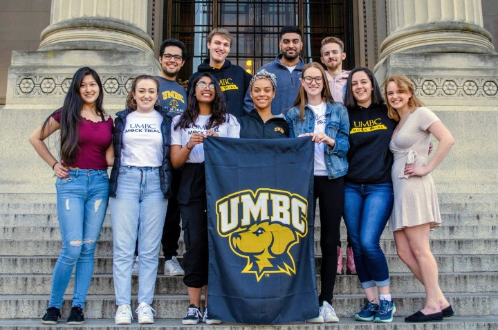 """Several young adults stand on steps in front of a building with large pillars. They hold a sign reading """"UMBC"""" and featuring a dog logo."""