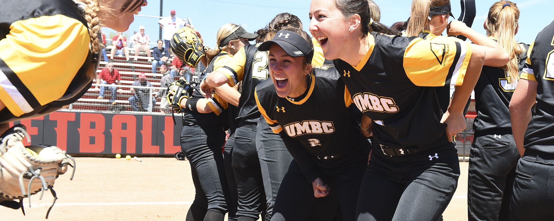 UMBC softball celebrates following the team's America East victory.