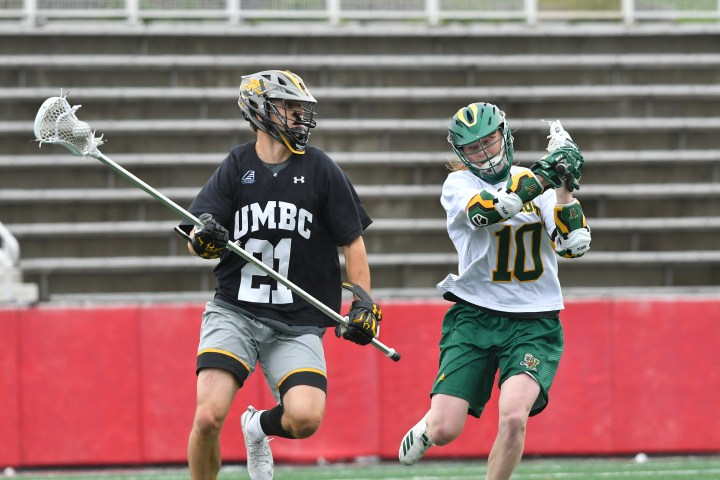 Two men's lacrosse players from different teams face off on the field