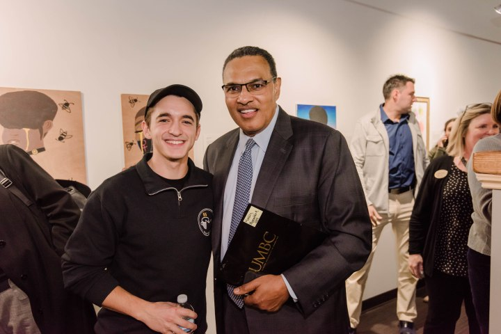 Student in OCA Mocha-branded sweater and cap poses with university president in suit and tie, in front of artwork/