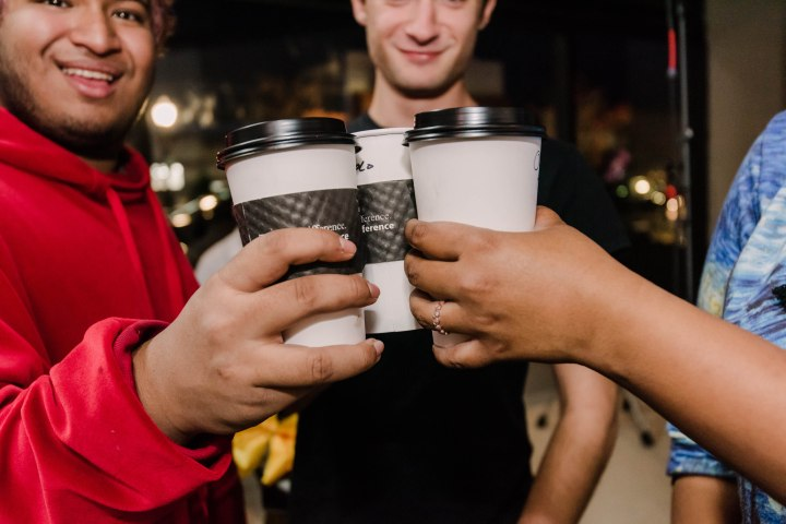 "Three people says ""cheers,"" clinking coffee cups in celebration."