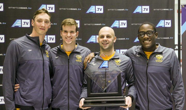 Four male swimmers wearing matching warm-up gear stand in front of an America East sign holding an America East trophy.