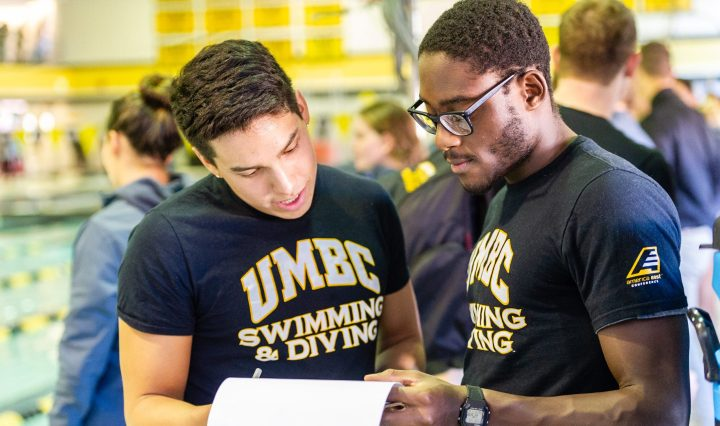 Two swimmers look at a paper together, wearing UMBC t-shirts next to a pool