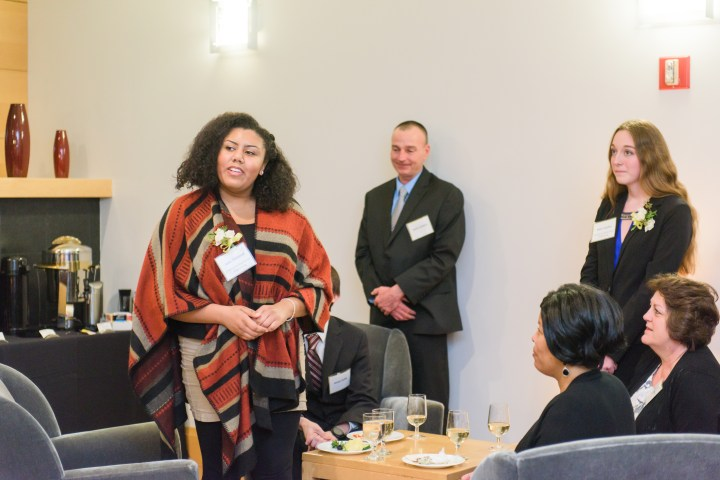 Young woman in dress clothes speaking at a wine/cheese reception.