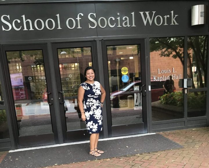 "Woman in black and white floral dress and sandals stands outside a building reading ""School of Social Work,"" smiling"