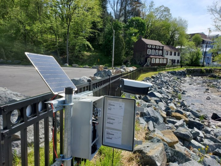 Box of electronic equipment with a solar power panel. Outdoor photo with road, plants, and homes in the background.