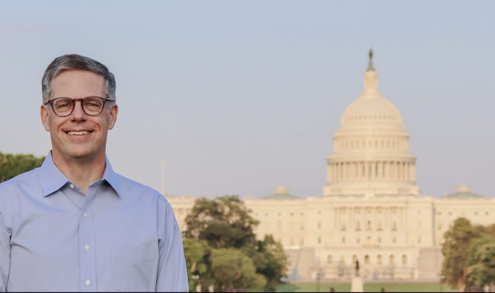 Man with greying short hair, wearing glasses and a blue dress shirt, smiles at the camera with the U.S. Capitol building in the background.