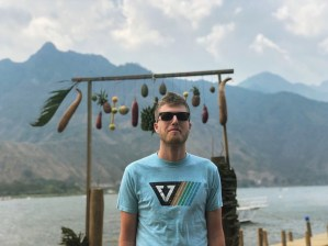 Young man with short brown hair, wearing black sunglasses and a light blue shirt with a multicolored design, stands in front of some objects hanging from a wooden pole and with mountains and a body of water behind him.