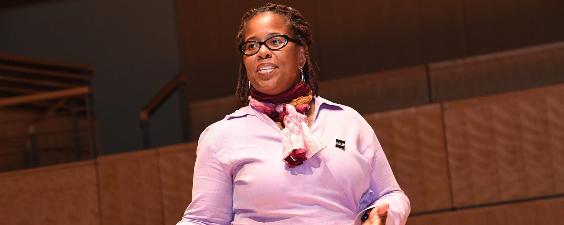 Black woman with black hair pulled back, wearing glasses, and a pink dress shirt and scarf looks towards the right.