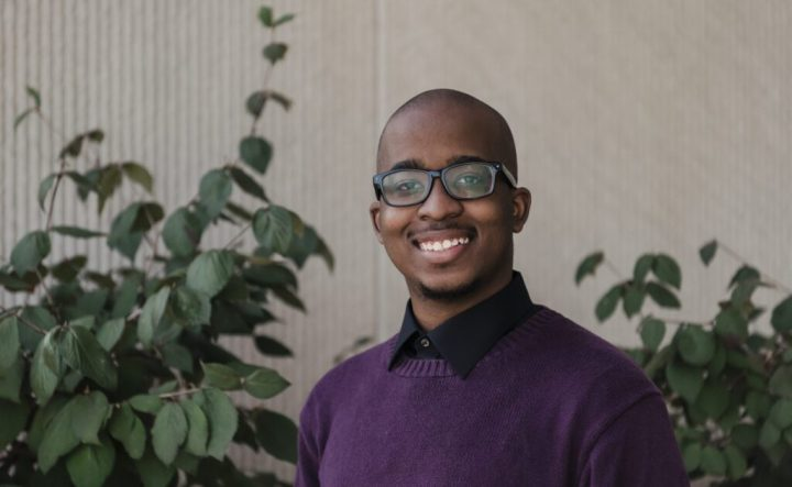Portrait of a young black man with glasses, wearing a black button-up shirt and a purple sweater. Plants in background.