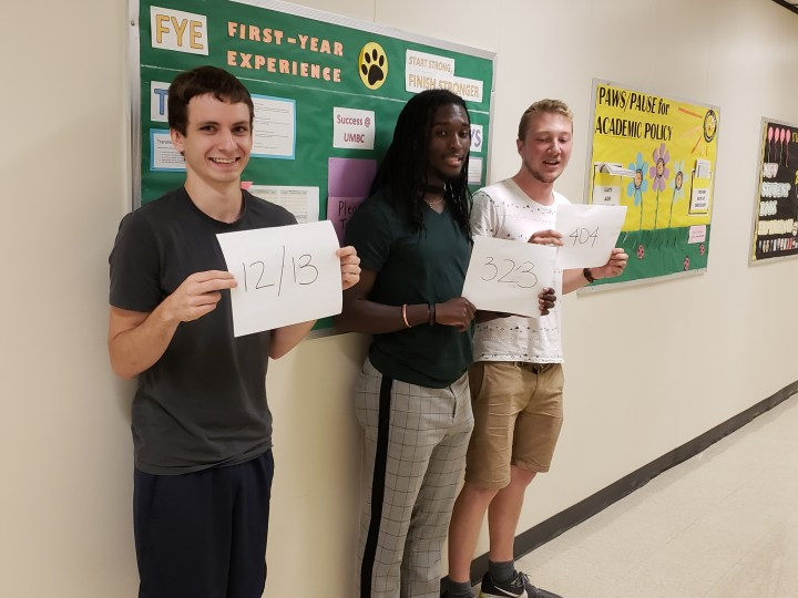 Three young men stand in a hallway holding up white pieces of paper with numbers written in black. There are colorful bulletin boards behind them.