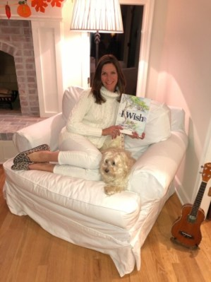 "White woman with long brown hair sits on a white couch, next to a small dog, holding a book titled ""I Wish"""