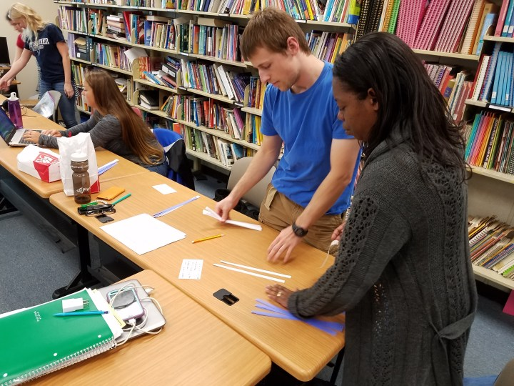 Three young women and one young man work around two wodden rectangular tables with white and blue strips of paper. There is a row of shelves behind them.