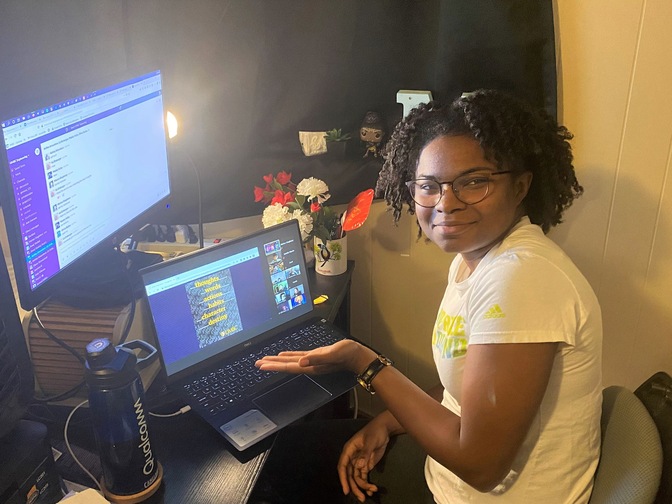 Young black woman with wire-frame glasses smiles into the camera, showing two computer screens.